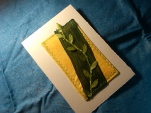 Cream card stock, yellow print fabric, green ribbon and light green leaves.