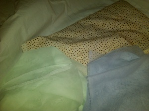 Red/off-white color print, light green and blue fabric, and underneath it all, the three and a half yards of muslin.