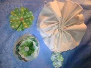 Upper left: paper flower. Upper right: Muslin Bottom right: Ribbon flower Bottom Left: 3 layers of fabric stitched with a button.