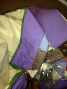 I loved sitting and sewing the binding. I am satisfied with the green contrasting with the purple.
