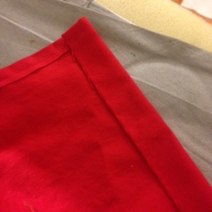 In the photo of the finished curtains, they look orange (I took that photo with my iPhone).   So I added the photo of the hems which shows off the bright red color.